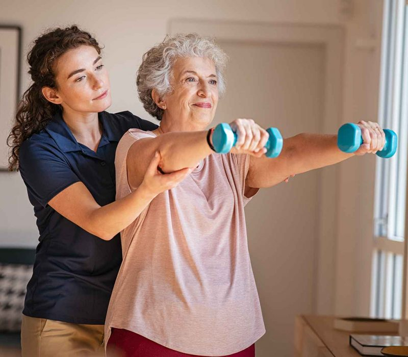 senior-woman-using-dumbbells-with-physiotherapist-9M87PE9.jpg